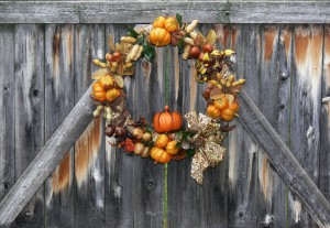 Decorative wreath depicting various autumn crops hanging on rustic wooden fence gate.