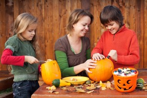 Woman helping kids to carve their pumpkin Halloween jack-o-lante