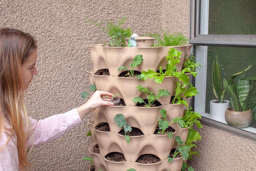 a woman planting in a vertical tower planter